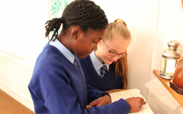 Pupils writing in the Book of Life