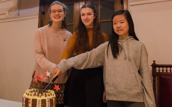 The Head Girl along with the oldest and youngest pupils at FHS cutting the cake