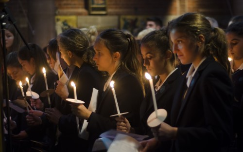 Girls share candlelight during the service