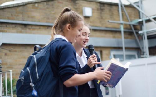 Girls reading poetry aloud