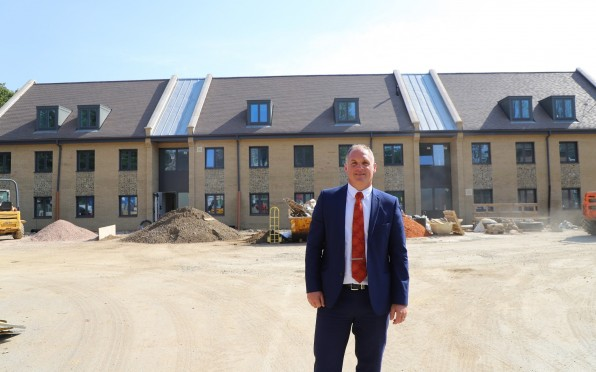 Dan Higgins (Chief Operating Officer) outside the new boarding house development