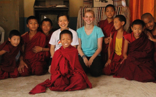Students gather round children that they have been helping in Nepal