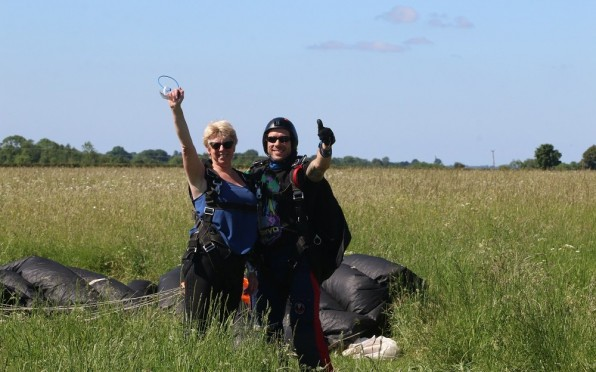 Nic Ross with skydiving instructor - thumbs up after a safe landing!